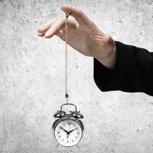 Close up of businessman holding clock on rope-782193-edited.jpeg