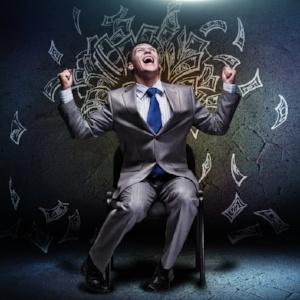 Joyful businessman sitting on chair under money rain-477336-edited.jpeg
