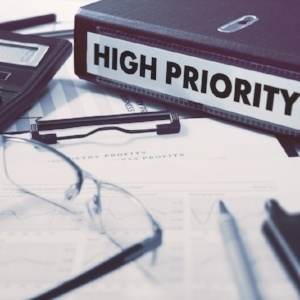 Ring Binder with inscription High Priority on Background of Working Table with Office Supplies, Glasses, Reports. Toned Illustration. Business Concept on Blurred Background.-005192-edited.jpeg